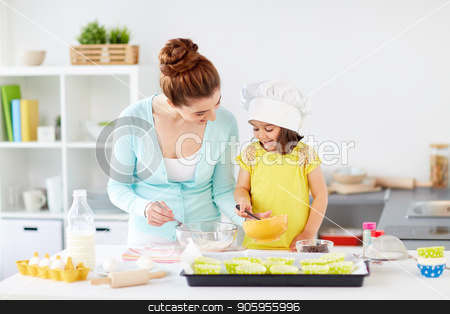 happy mother and daughter baking muffins at home stock photo, family, cooking, baking and people concept - happy mother and little daughter making batter for muffins at home kitchen by Syda Productions