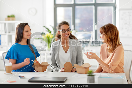 happy businesswomen eating take out food at office stock photo, business lunch and people concept - happy businesswomen eating take out food and talking at office by Syda Productions