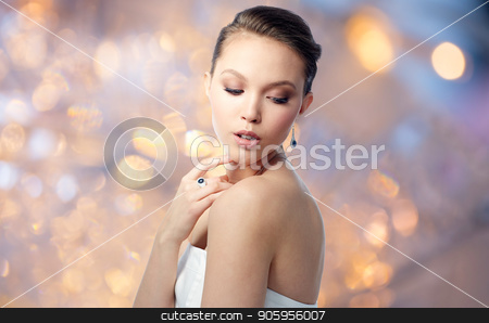 beautiful woman with earring and finger ring stock photo, beauty, jewelry, people and luxury concept - beautiful asian woman or bride with earring and finger ring over holidays lights background by Syda Productions