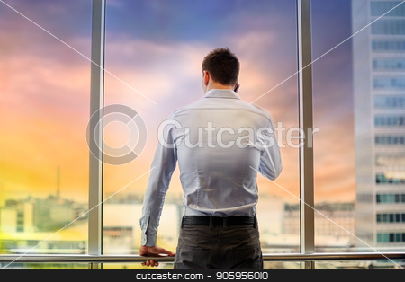 businessman calling on smartphone at office window stock photo, business, technology and people concept - businessman calling on smartphone and looking out office window over city view background by Syda Productions