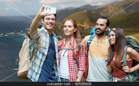 friends with backpack taking selfie by smartphone stock photo, technology, travel, tourism, hike and people concept - group of smiling friends with backpacks taking selfie by smartphone over bixby creek bridge on big sur coast of california background by Syda Productions