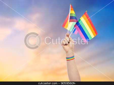 hand with gay pride rainbow flags and wristband stock photo, lgbt, same-sex relationships and homosexual concept - close up of male hand with gay pride awareness wristband holding rainbow flags over evening sky background by Syda Productions