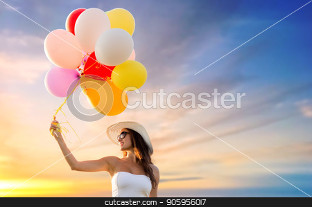 woman in sunglasses with balloons over sunset sky stock photo, happiness, summer and people concept - smiling young woman wearing sunglasses with balloons over sunset sky background by Syda Productions