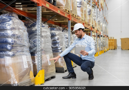 happy businessman with tablet pc at warehouse stock photo, wholesale, logistic business, export and people concept - happy businessman in helmet with tablet pc computer checking goods at warehouse by Syda Productions