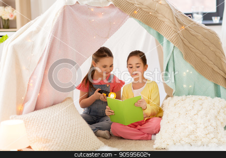 little girls reading book in kids tent at home stock photo, childhood, friendship and hygge concept - happy little girls reading book with torch light in kids tent or teepee at home by Syda Productions