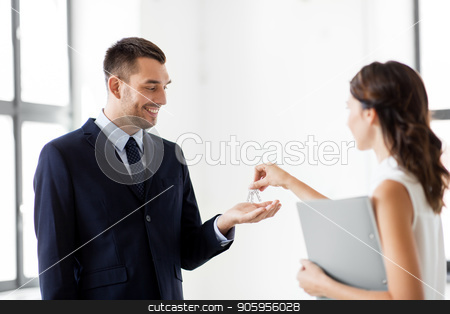 realtor giving key to customer at new office stock photo, real estate business, sale and people concept - realtor giving key to customer or new office owner by Syda Productions