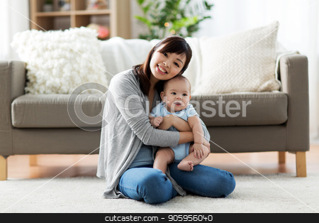 happy young mother with little baby at home stock photo, family and motherhood concept - happy smiling young asian mother with little baby at home by Syda Productions