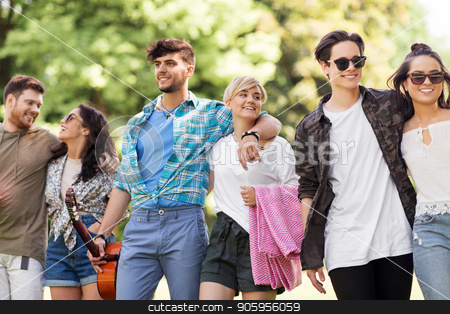 friends with guitar and picnic blanket at park stock photo, friendship and leisure concept - group of happy friends with guitar and picnic blanket at summer park by Syda Productions