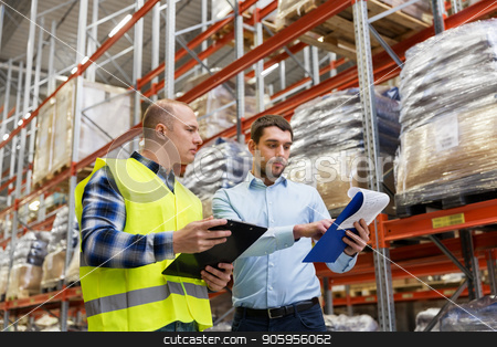 worker and businessman with clipboard at warehouse stock photo, wholesale, logistic business and people concept - manual worker and businessman with clipboards at warehouse by Syda Productions