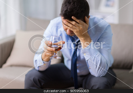 drunk man with glass of alcohol at home stock photo, alcoholism, alcohol addiction and people concept - male alcoholic drinking brandy at home by Syda Productions
