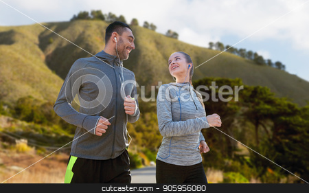 couple with earphones running over big sur stock photo, fitness, sport and technology concept - happy couple running and listening to music in earphones over big sur hills background in california by Syda Productions