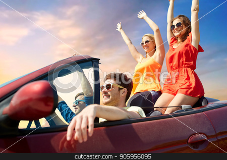friends driving in convertible car over sky stock photo, summer holidays, road trip and travel concept - happy friends driving in convertible car and waving hands over sky background by Syda Productions