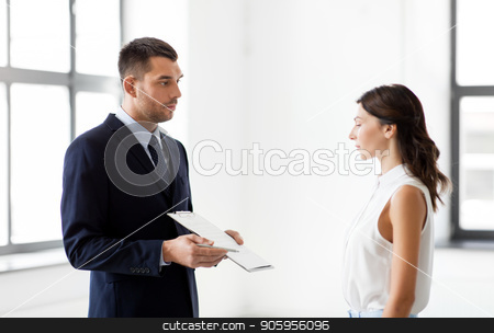 realtor showing contract document to customer stock photo, real estate business, sale and people concept - male realtor with clipboard showing contract document to customers at new office room by Syda Productions