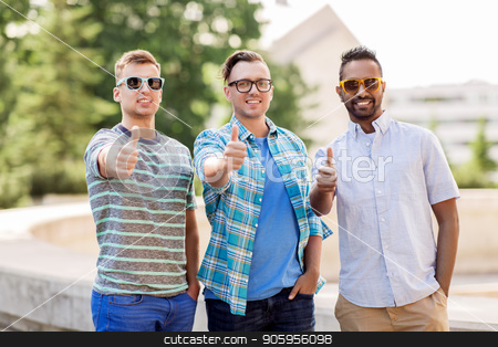 happy young men in sunglasses showing thumbs up stock photo, male friendship, summer and eyewear - happy young men in sunglasses outdoors showing thumbs up by Syda Productions