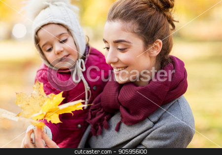 mother and little daughter with autumn leaves stock photo, family, season and people concept - happy mother and little daughter with maple leaves at autumn park by Syda Productions