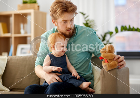 father and baby daughter with teddy bear at home stock photo, family, fatherhood and people concept - happy red haired father and little baby daughter playing with teddy bear at home by Syda Productions