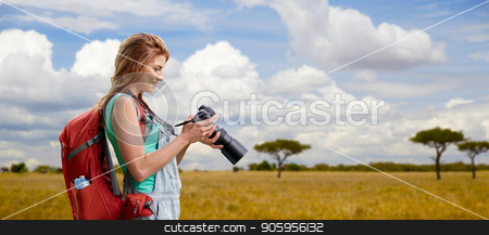 woman with backpack and camera over savannah stock photo, travel, tourism and photography concept - happy young woman with backpack and camera photographing over african savannah background by Syda Productions