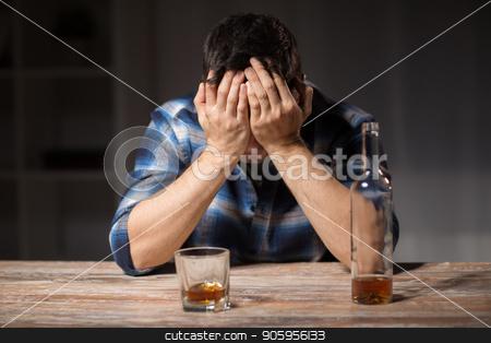 alcoholic with bottle drinking whiskey at night stock photo, alcoholism, alcohol addiction and people concept - male alcoholic with bottle and glass drinking whiskey at night by Syda Productions