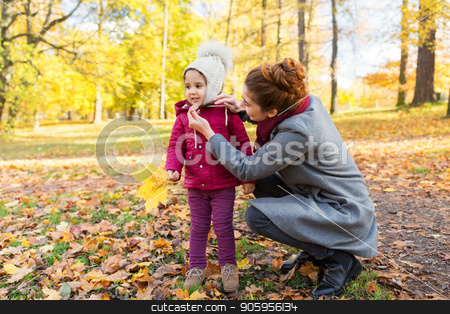 happy family with autumn leaves at park stock photo, family, season and people concept - happy mother and little daughter with autumn leaves at park by Syda Productions