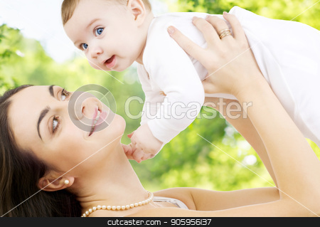 mother with baby over green natural background stock photo, family and motherhood concept - happy smiling young mother with little baby over green natural background by Syda Productions