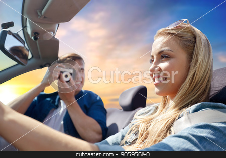 happy couple with camera driving in cabriolet car stock photo, leisure, road trip, travel and people concept - happy couple driving in cabriolet car and taking picture by film camera over evening sky background by Syda Productions