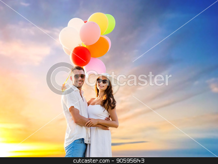 happy couple with balloons over sunset sky stock photo, love, summer, dating and birthday concept - happy couple wearing sunglasses with balloons hugging over sunset sky background by Syda Productions