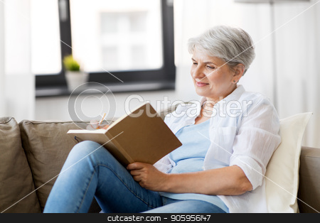 senior woman writing to notebook or diary at home stock photo, age, leisure and people concept - happy senior woman writing to notebook or diary at home by Syda Productions