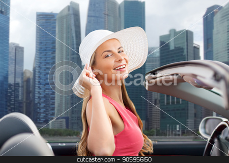 woman in hat in convertible car over singapore stock photo, travel, road trip and people concept - happy young woman wearing sun hat in convertible car over singapore city skyscrapers background by Syda Productions