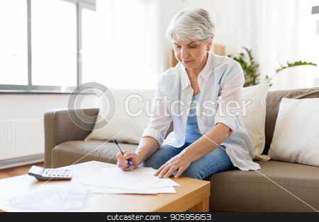 senior woman with papers and calculator at home stock photo, business, savings, annuity insurance, age and people concept - senior woman with papers or bills and calculator writing at home by Syda Productions