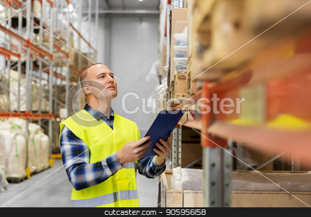 warehouse worker with clipboard in safety vest stock photo, logistic business, shipment and people concept - male worker or supervisor with clipboard in reflective safety vest at warehouse by Syda Productions