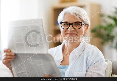 portrait of senior woman reading newspaper at home stock photo, age and people concept - portrait of happy senior woman reading newspaper at home by Syda Productions