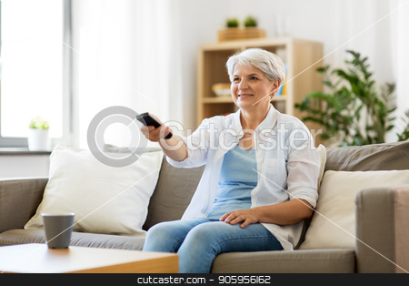 senior woman with remote watching tv at home stock photo, people, television and entertainment concept - senior woman in eyeglasses with remote control watching tv at home by Syda Productions