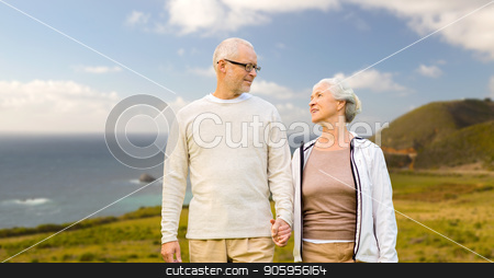 happy senior couple over big sur coast stock photo, old age, tourism, travel and people concept - happy senior couple holding hands over big sur coast of california background by Syda Productions
