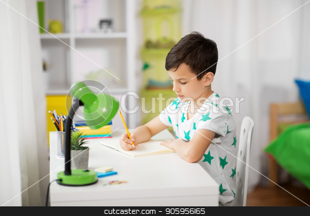 little boy writing to notebook at home stock photo, education, childhood and school concept - little boy sitting at desk and writing to notebook at home by Syda Productions