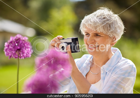 senior woman with camera photographing flowers stock photo, photography, leisure and people concept - happy senior woman with camera photographing flowers blooming at summer garden by Syda Productions