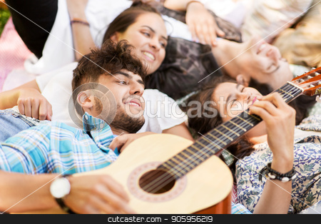 friends playing guitar and chilling on blanket stock photo, friendship, leisure and summer concept - group of happy smiling friends playing guitar and chilling on picnic blanket by Syda Productions
