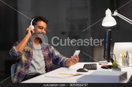 man with headphones and smartphone at night office stock photo, deadline, technology and people concept - happy creative man with headphones listening to music by smartphone and computer at night office by Syda Productions