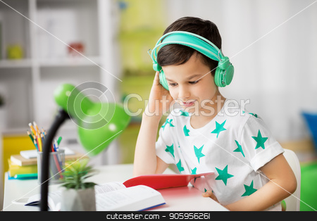 student boy in headphones reading book at home stock photo, education, childhood and school concept - student boy in headphones reading book at home by Syda Productions
