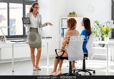 woman showing tablet pc to business team at office stock photo, business, technology and people concept - businesswoman showing tablet pc computer to female team at office by Syda Productions