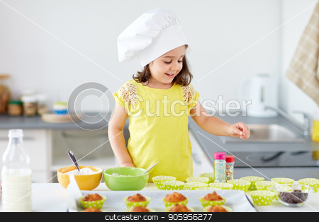 little girl in chefs toque baking muffins at home stock photo, family, cooking and people concept - little girl in chefs toque baking muffins or cupcakes with sprinkles at home by Syda Productions