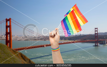hand with gay pride rainbow flags and wristband stock photo, lgbt, same-sex relationships and homosexual concept - close up of male hand with gay pride awareness wristband holding rainbow flags over golden gate bridge in san francisco bay background by Syda Productions