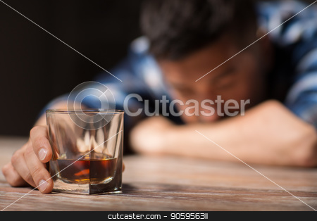 drunk man with glass of alcohol on table at night stock photo, alcoholism, alcohol addiction and people concept - male alcoholic with glass of whiskey lying or sleeping on table at night by Syda Productions