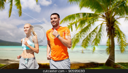 smiling couple running over tropical beach stock photo, fitness, sport and healthy lifestyle concept - smiling couple with heart-rate watch running over tropical beach background in french polynesia by Syda Productions