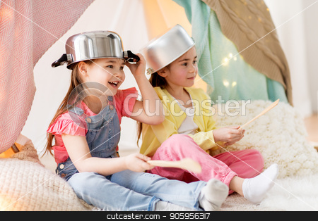 girls with kitchenware playing in tent at home stock photo, childhood and hygge concept - happy little girls with cooking pots playing in kids tent at home by Syda Productions