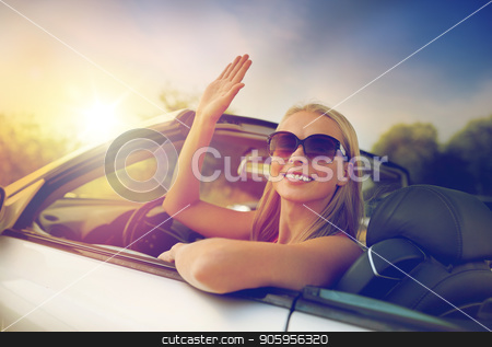 happy young woman in convertible car waving hand stock photo, travel, road trip and people concept - happy young woman in convertible car waving hand by Syda Productions