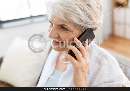senior woman calling on smartphone at home stock photo, technology, communication and people concept - close up of happy senior woman calling on smartphone at home by Syda Productions