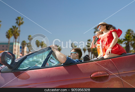 friends driving in convertible car at venice beach stock photo, summer holidays, road trip and travel concept - happy friends driving in convertible car over venice beach background in california by Syda Productions