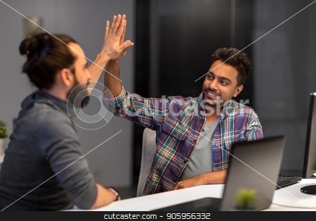 creative team making high five at night office stock photo, deadline, teamwork and success concept - creative team with computers making high five at night office by Syda Productions
