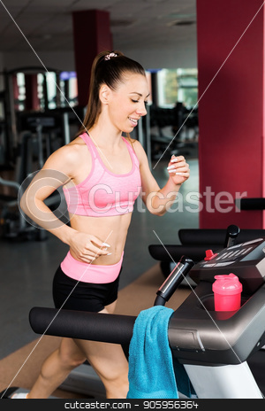 girl at the running track stock photo, slim beautiful sporty woman excercising at the running track in the gym. Concept of cardio exercises and healthy way of life by Oleh