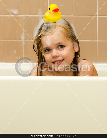 Rubber ducky on her head stock photo, Young girl playing in the tub covered in suds and has a rubber duck on her head by txking